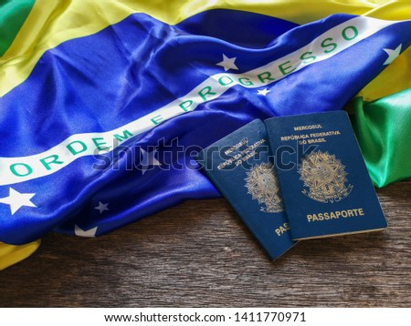 Brazilian flag with Brazilian passport and wooden background