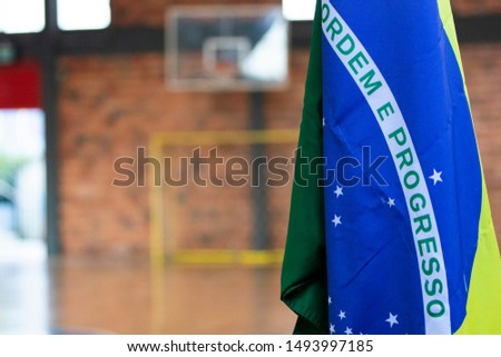 "Brazilian flag with the phrase ""order and progress"" hanging from a pole inside indoors stadium environment."