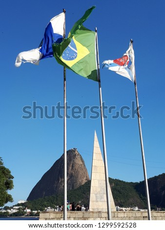 Brazilian flags waving with mountains behind