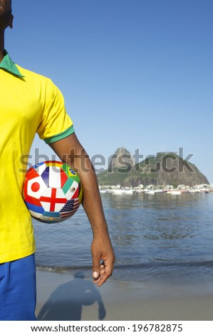 Brazilian football player standing with international country flag soccer ball in front of Sugarloaf Pao de Acucar Mountain and Guanabara Bay in Rio de Janeiro Brazil