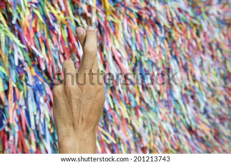 Brazilian hand fingers crossed for luck in front of colorful religious Brazilian wish ribbons fita do Bonfim in Salvador Bahia Brazil