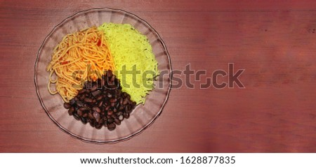 Brazilian lunch.  Brown background.  Brown.  copy space.  bean.  rice.  spaghetti.  done dish.  food.  blurred background.  out door.
