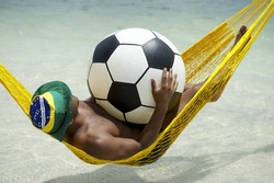 Brazilian man relaxing in beach hammock with large football soccer ball