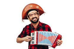 Brazilian man wearing traditional clothes for Festa Junina - June festival - playing accordion