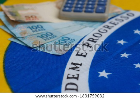 Brazilian money and calculator on top of Brazilian flag. Brazilian salary concept. Economy, investment.