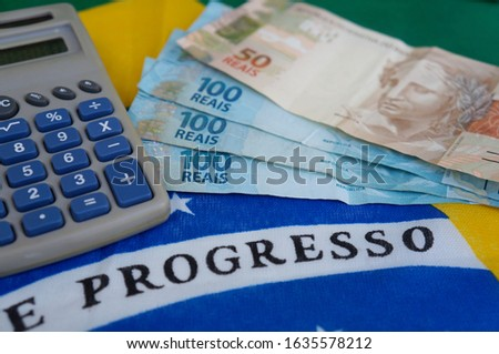 Brazilian money and calculator on top of Brazilian flag. Brazilian salary concept. Translation: Progress.