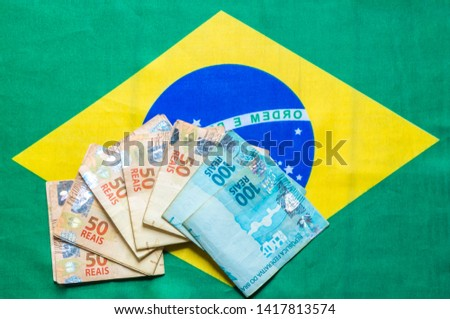 Brazilian money bills on top of the national flag mirrored hundred real notes and 50 reais