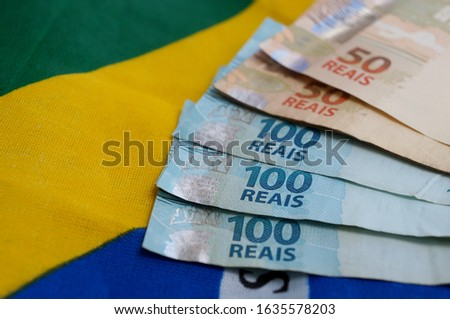 Brazilian money on top of Brazilian flag. Brazilian salary concept.