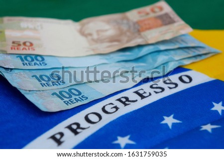 Brazilian money on top of Brazilian flag. Brazilian salary concept. Translation: Progress.
