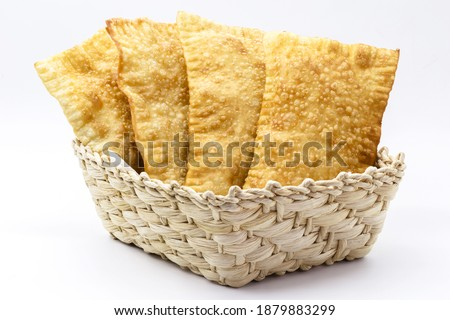 Brazilian pastry, traditional pastry called fried meat pastry, in straw basket, isolated on white background, copyspace
