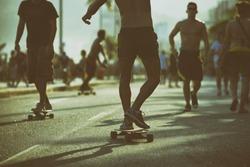 Brazilian skaters skate along the Ipanema Beach beachfront Avenida Vieira Souto road in a toned scene in Rio de Janeiro, Brazil