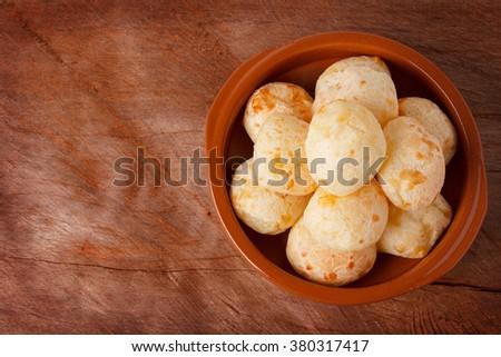 Brazilian snack cheese bread (pao de queijo) in bowl on wooden table. Selective focus