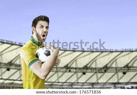 Brazilian soccer player holding a ball celebrates with the fans on the stadium