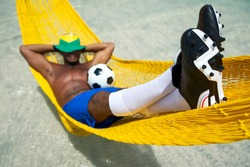 Brazilian soccer player in his boots relaxing in a beach hammock with a football resting in his lap