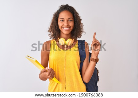 Brazilian student woman wearing backpack holding notebook over isolated white background surprised with an idea or question pointing finger with happy face, number one