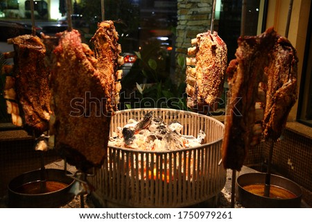 Brazilian style beef ribs Barbecue grill on skewers around fire stove at a churrascaria steakhouse in Sao Paulo, Brazil.