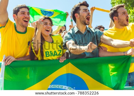 Brazilian supporters celebrating at stadium with flags. Group of fans watching a match and cheering team Brazil. Sport and lifestyle concepts.