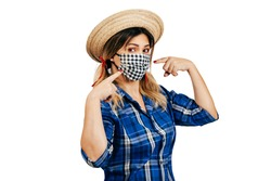 Brazilian woman wearing typical clothes for the Festa Junina and protection mask to prevent COVID-19