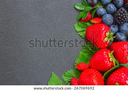 brder  of fresh  wild berries and  leaves with copy space  on black stone background