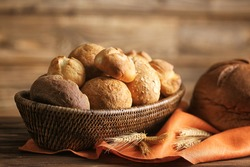 Bread and lots of fresh bread buns in a basket on a wooden table