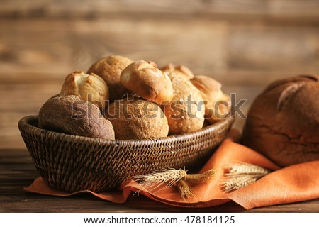 Bread and lots of fresh bread buns in a basket on a wooden table #478184125