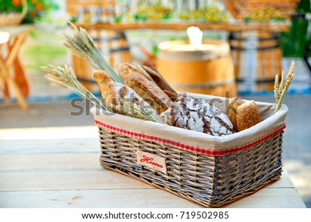 Bread basket outdoors on a wooden table in a street cafe, closeu #719502985