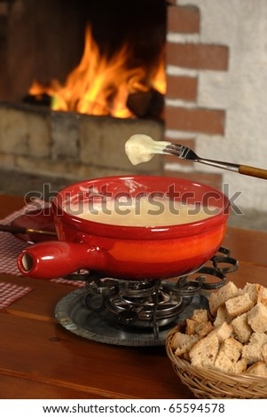 Bread being dipped into the melted cheese in the fondue bowl.