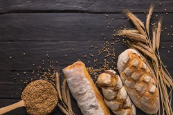 Bread border on wood with copy space background. Brown and white whole grain loaves still life composition with wheat ears scattered around. Bakery and grocery food store concept.