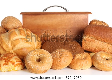 Bread box surrounded by bread and buns.