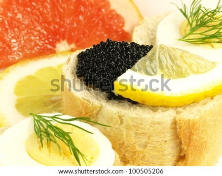 Bread, caviar, egg, and slices of citrus