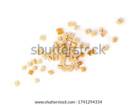 Bread croutons splash isolated on white background top view. Crispy bread cubes, dry crumbs, rusks, crouton or white roasted crackers cube heap