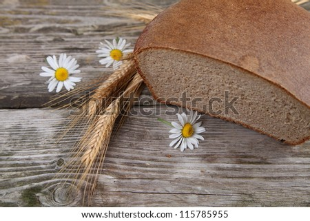 Bread, ears and daisies on a wooden table. Still life.