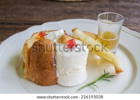 Bread grill and ice cream on white plate in restaurant.