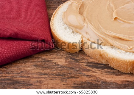 Bread is smeared Peanut butter - a component for a sweet sandwich.