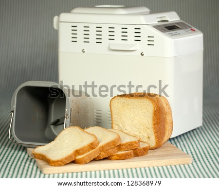 Bread machine with pan and fresh white bread at home.