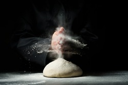 Bread making. Knead the dough in a cloud of flour dust. Food preparation concept on dark background