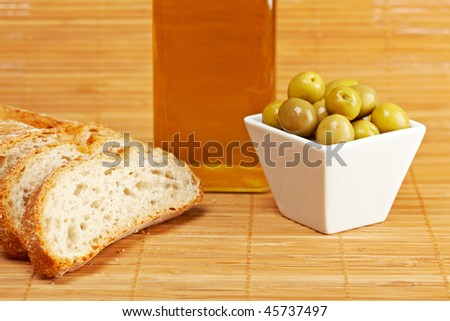 Bread, olive oil bottle and some olives on wooden background. Shallow depth of field