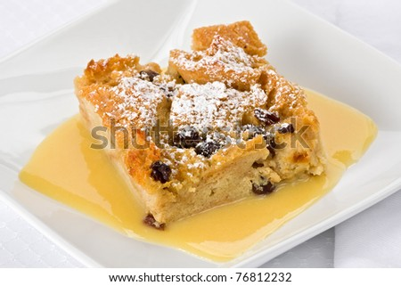 Bread pudding with bourbon sauce on a square plate.