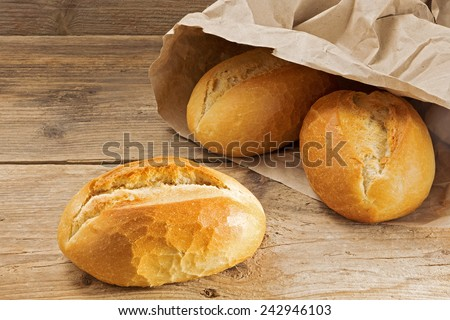 bread rolls in a paper bag on a rustic wooden table, fresh from the bakery for breakfast