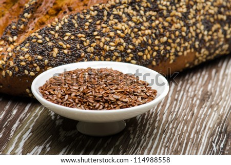 Bread seeds and flax seeds on wooden table