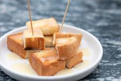 Bread slice with sweetened condensed milk close up. Sweetened condensed milk in butter bread. Bread toast with butter sugar and condensed milk in white plate. Close-up bread toast with butter.