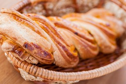 Bread twirl in the basket on a wooden table.