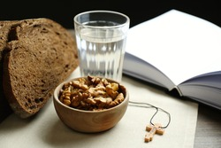 Bread, walnuts, water, Bible and crucifix on table. Great Lent season