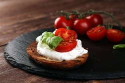 Bread with cream cheese and tomato for lunch table. Sharing antipasti on party or summer picnic time over wooden rustic background.