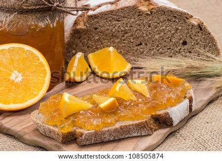 Bread with Orange Jam and fresh fruits on rustic background