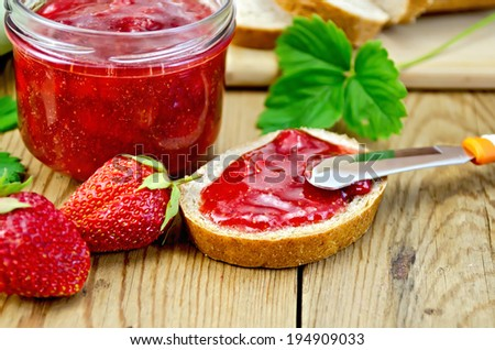Bread with strawberry jam a jar of jam knife strawberries on a wooden boards background