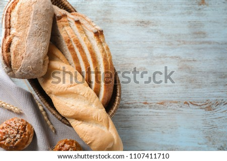 Breadbasket with different bakery products on wooden background