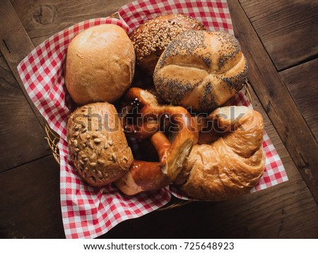 Breadbasket with red and white checkered napkin filled with traditional German breakfast buns such as poppyseed kaiser rolls, sunflower seed rolls, whole wheat bread, pretzels and croissants