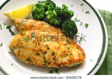Breaded and herbed chicken breast fillet, served with broccoli and lemon.  Delicious chicken schnitzel.