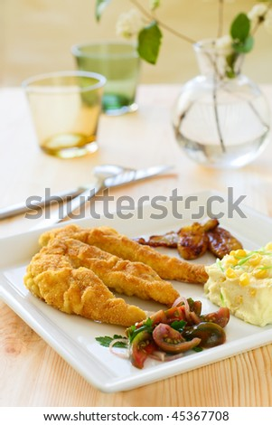Breaded chicken breast fillet, served with tomato salad and mashed potatoes